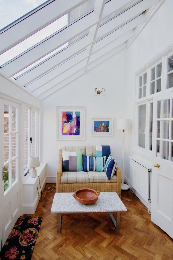 una veranda semplice e moderna con un piccolo divano di vimini con cuscini colorati, opere d'arte e un tavolino da caffè