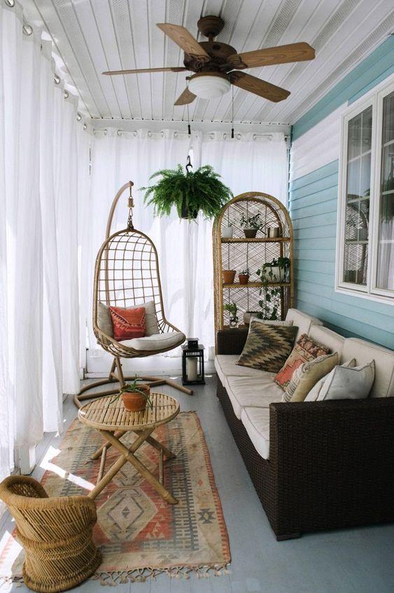 una piccola veranda boho con un divano scuro, mobili in vimini e una sedia sospesa più vegetazione in vaso