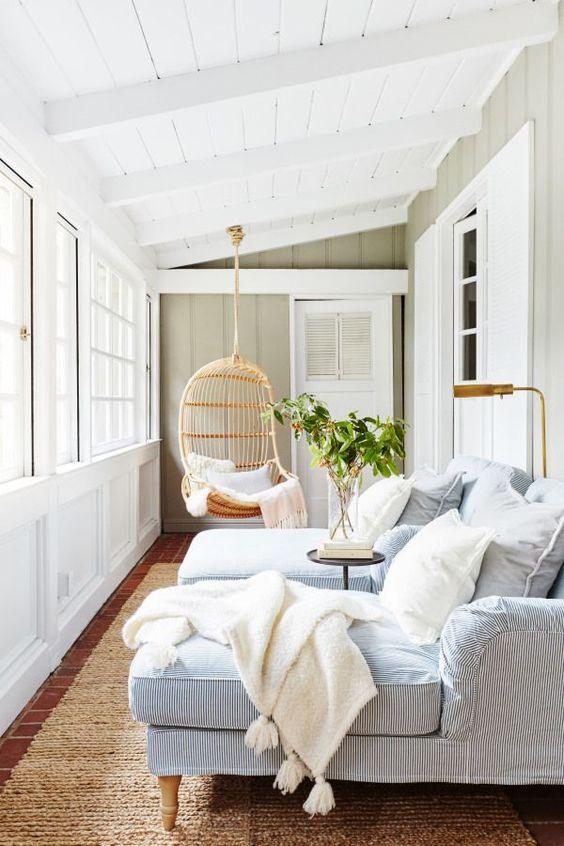 una piccola veranda rilassante con sedie a sdraio a strisce blu, una lampada, un tavolo e una sedia di vimini sospesa