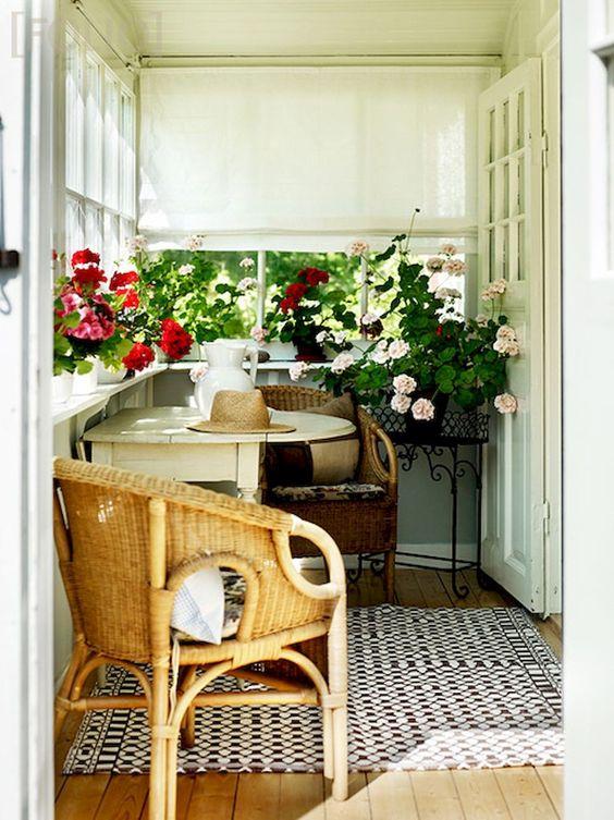 una piccola veranda accogliente con sedie di vimini e un tavolo pieghevole, con molte fioriture in vaso e sfumature romane