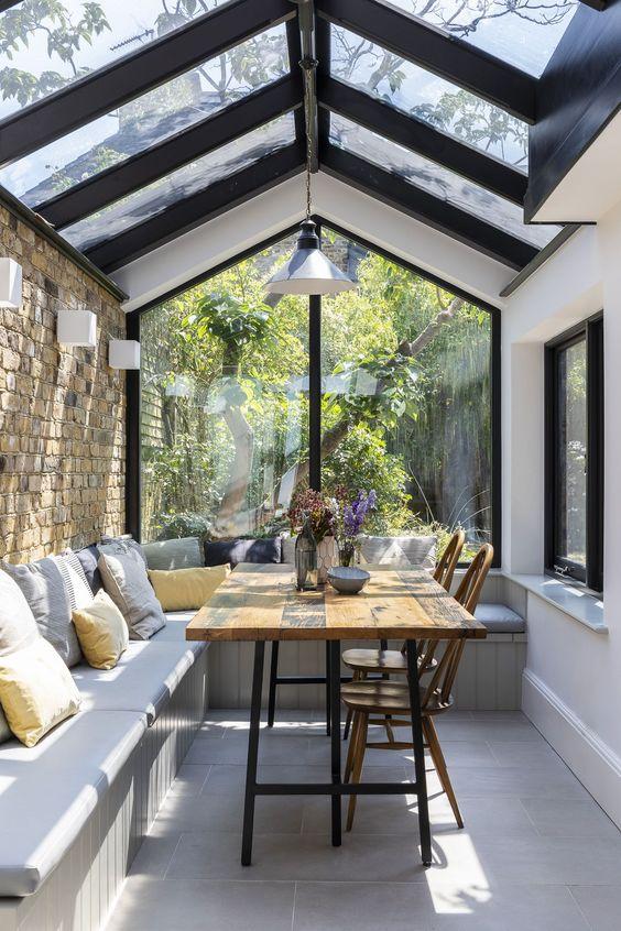 una piccola veranda con zona pranzo, lampade da parete e a sospensione, con una grande panca a forma di L e un tavolo da pranzo