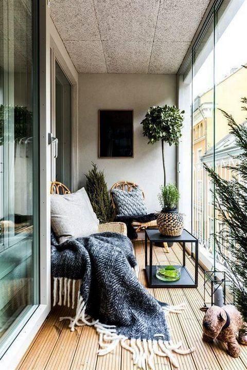 una veranda moderna con un'atmosfera boho: un paio di lettini in vimini, un tavolo, una lanterna e una vegetazione in vaso