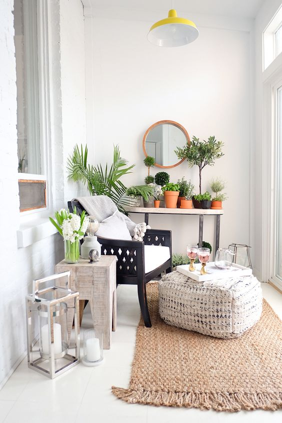 una piccola veranda accogliente con tocchi boho, un tappeto di iuta e pouf, sedie in legno e molta vegetazione in vaso e lanterne