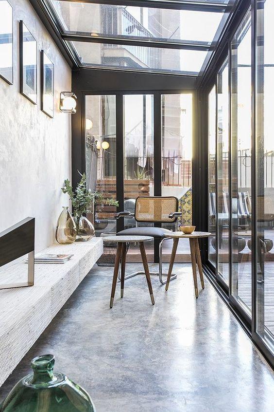 una veranda moderna con mobili laconici in legno e vimini, una lunga panchina, opere d'arte e lampade