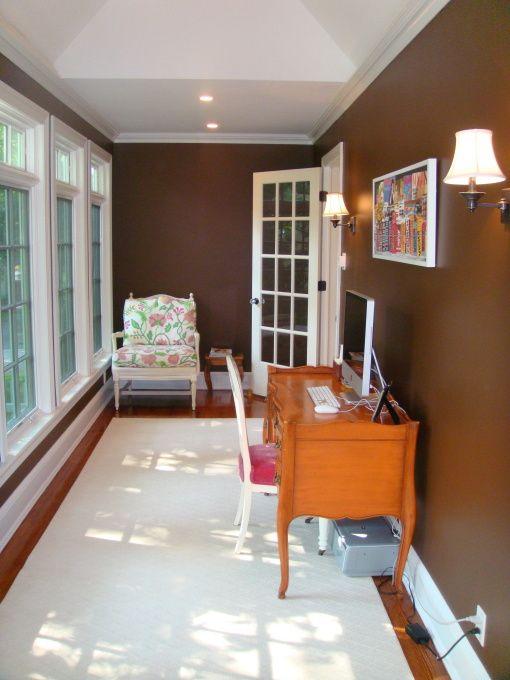 una piccola veranda colorata trasformata in un ufficio a casa, con mobili e stampe di ispirazione vintage