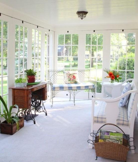 una splendida veranda con mobili da giardino forgiati, una grande panchina bianca, una scrivania vintage e un cestino