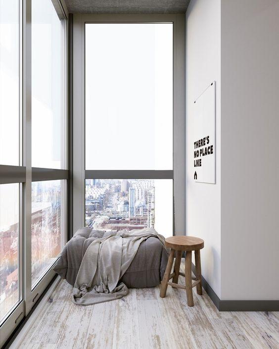 una veranda minimalista con un comodo divano letto, una coperta e uno sgabello è tutto ciò di cui hai bisogno per rilassarti