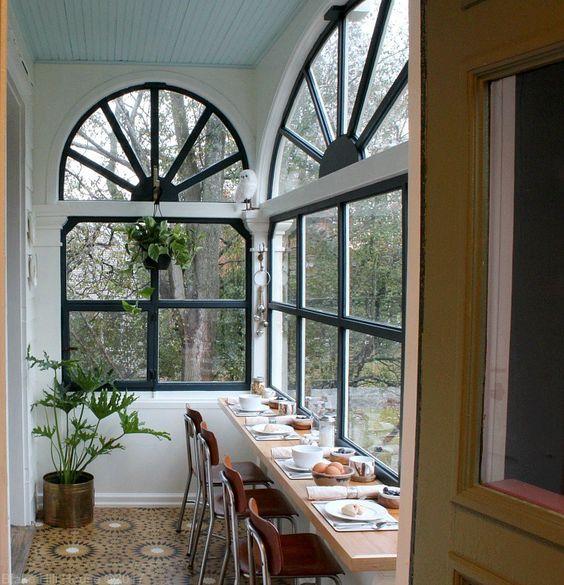 una piccola veranda trasformata in uno spazio per i pasti, con un tavolo sul davanzale della finestra e piante in vaso