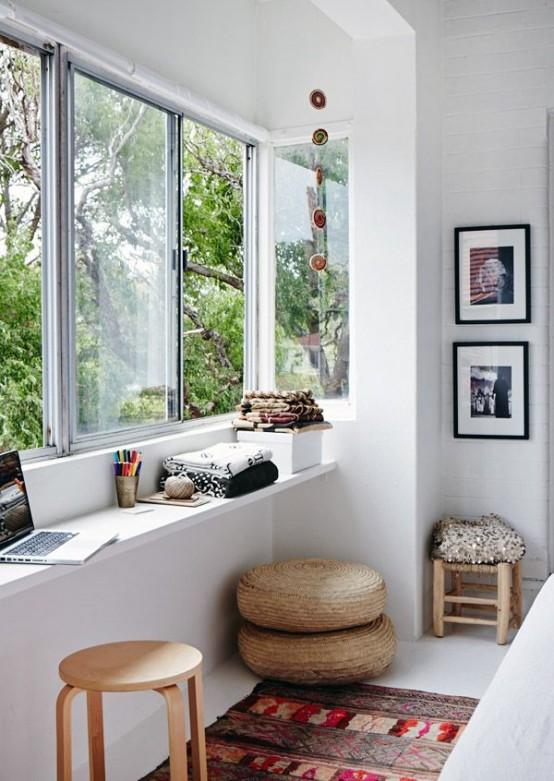 uno spazio veranda contemporaneo come un ufficio a casa o uno spazio artistico con una scrivania sul davanzale della finestra, alcuni sgabelli e pouf