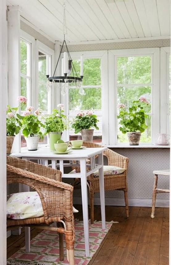 una veranda con uno spazio per mangiare un tavolo bianco e sedie di vimini e molti fiori in vaso