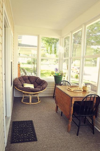 una veranda da pranzo / spazio di gioco con un tavolo pieghevole, alcune sedie e una sedia rotonda imbottita