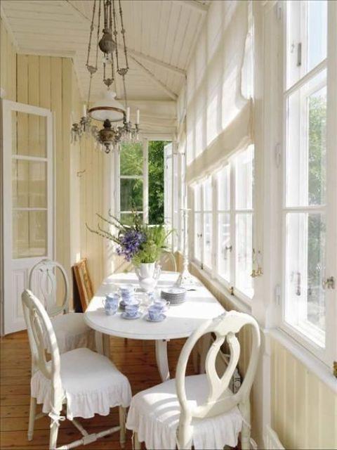 un angolo veranda di ispirazione vintage con uno spazio da tè con mobili sofisticati e lampade vintage