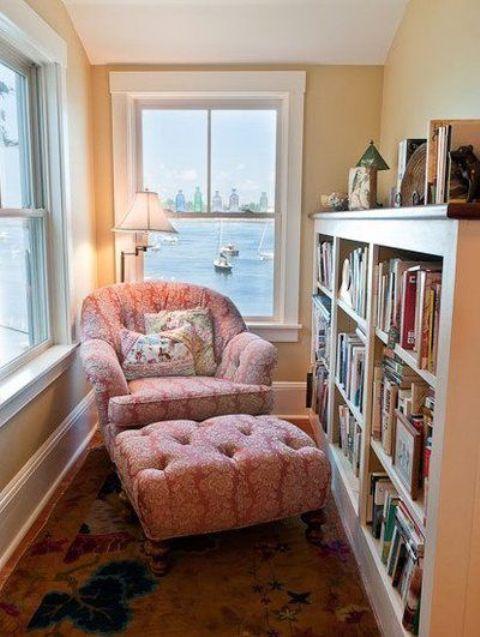 una veranda trasformata in un angolo lettura con una grande libreria e una poltrona rosa più una lampada