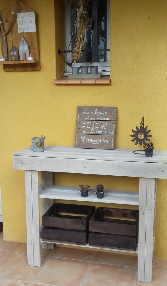 una semplice ed elegante consolle in legno di pallet dipinto di grigio è dotata di due ripiani per riporre gli oggetti