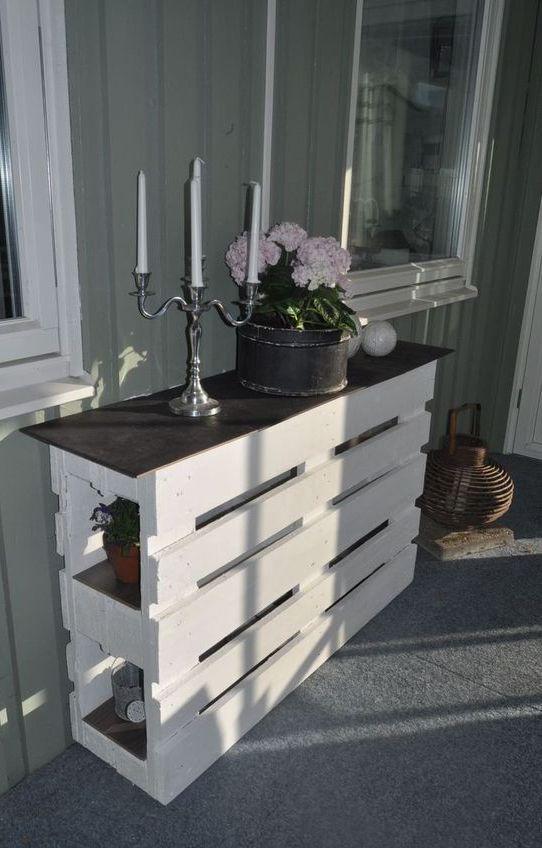 un'elegante consolle con pallet di due pezzi dipinti di bianco e un piano del tavolo nero sembra fresca ed elegante
