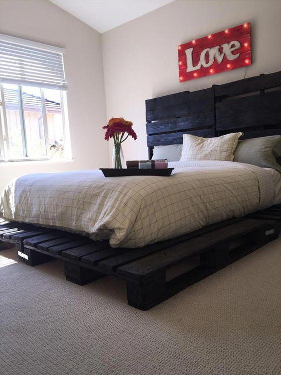 un letto pallet dipinto di scuro sembra insolito e più duro di un normale letto macchiato di luce