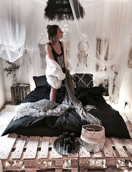 un letto pallet con luci all'interno e sopra per una camera da letto boho chic, un baldacchino in tulle sopra il letto lo rende più fresco