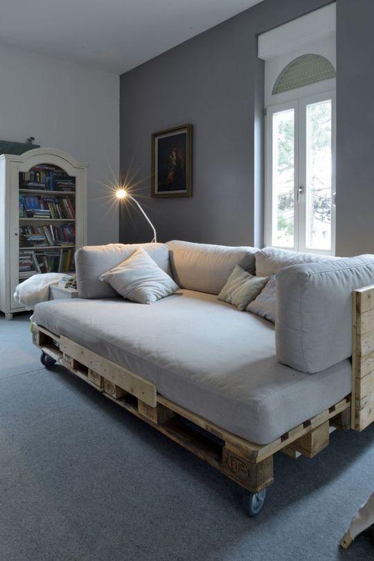 un divano letto in pallet con schienale e ruote, dotato di un comodo materasso e cuscini sulla parte superiore
