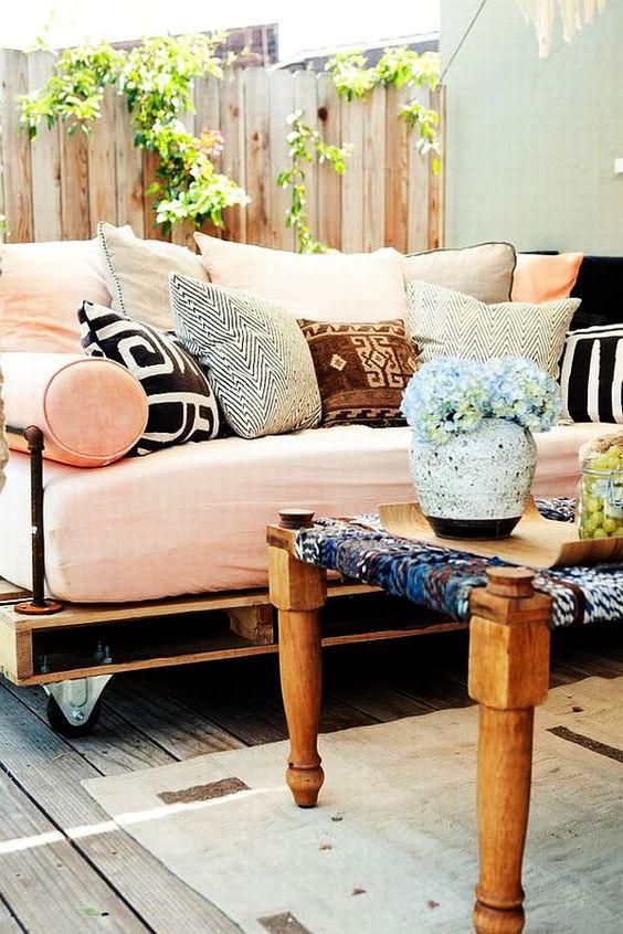un lettino da esterno con pallet su ruote con un morbido materasso e tanti cuscini colorati e stampati
