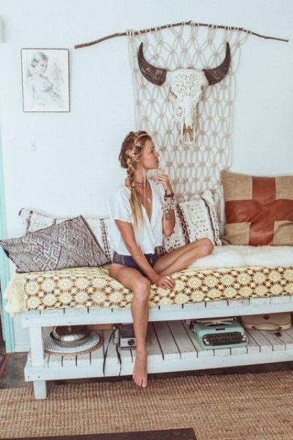 un divano letto costruito con pallet presenta uno scaffale per riporre e molti tessuti colorati e stampati per uno spazio boho