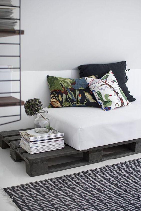 un divano letto in pallet macchiato di scuro con un comodo materasso e cuscini stampati è una bella idea per un soggiorno