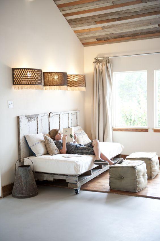 un angolo lettura dotato di un divano letto pallet su ruote e una testiera coordinata conferisce un tocco shabby chic