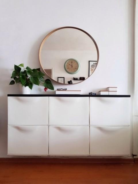 un'elegante console galleggiante da ingresso con un piano del tavolo nero è un'idea contemporanea chic, che si adatta anche a un piccolo spazio