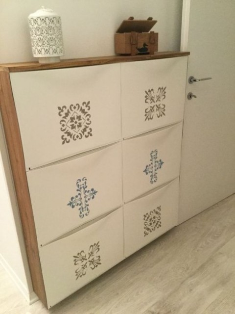 una scarpiera IKEA Trones decorata con adesivi colorati e con un piano di lavoro a cascata in legno per un ingresso