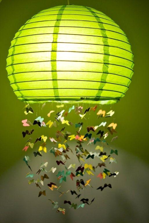 un colorato paralume Regolit con alcune farfalle di carta attaccate è una decorazione stravagante