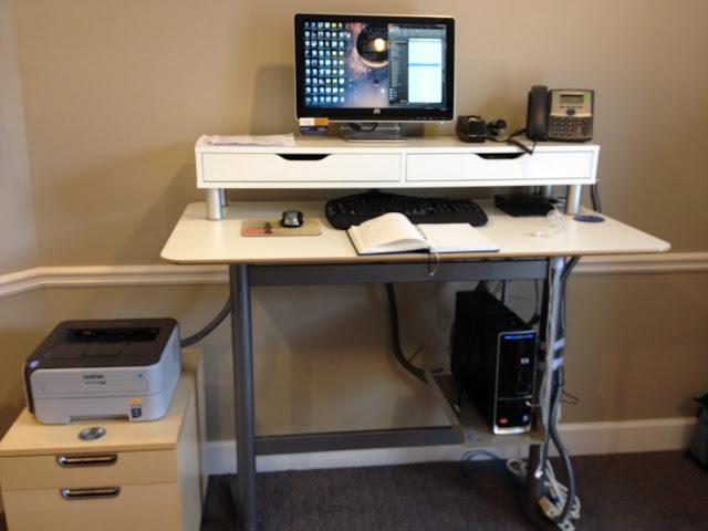 una moderna postazione di lavoro in piedi con un'unità Ekby Alex montata su di essa per creare una scrivania in piedi