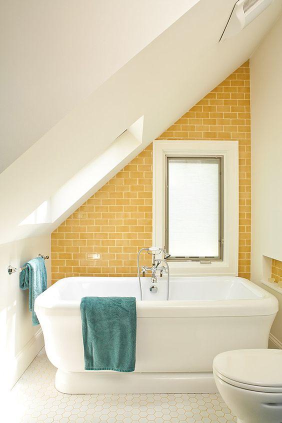 un piccolo bagno mansardato con un muro di piastrelle giallo sole che lo rende più accogliente