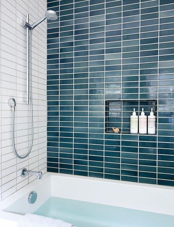 un muro di piastrelle verde acqua lungo e stretto aggiunge colore al bagno facendolo sentire come un mare