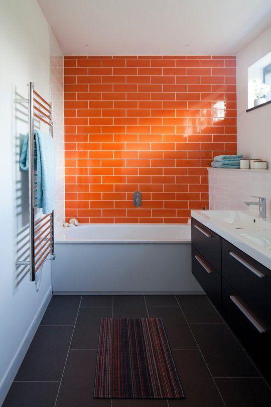 un tocco luminoso in bagno è fatto con un muro di piastrelle arancione brillante