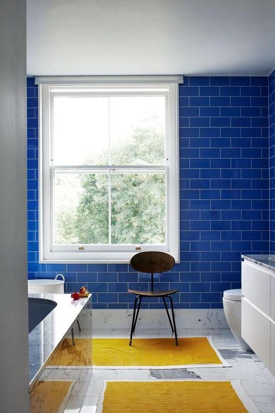 le piastrelle blu audaci della metropolitana sul muro fanno una dichiarazione e aggiungono un vantaggio poiché le piastrelle della metropolitana sono una tendenza calda