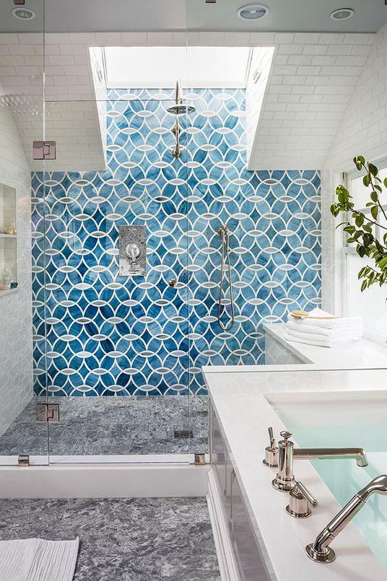 un audace muro di piastrelle a mosaico blu sotto la doccia è un'idea audace per aggiungere colore e motivo al bagno