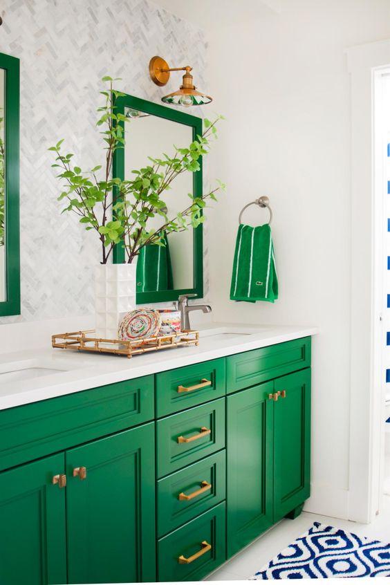 una brillante vanità smeraldo accentata con maniglie in ottone e cornici e asciugamani coordinati sopra la vanità