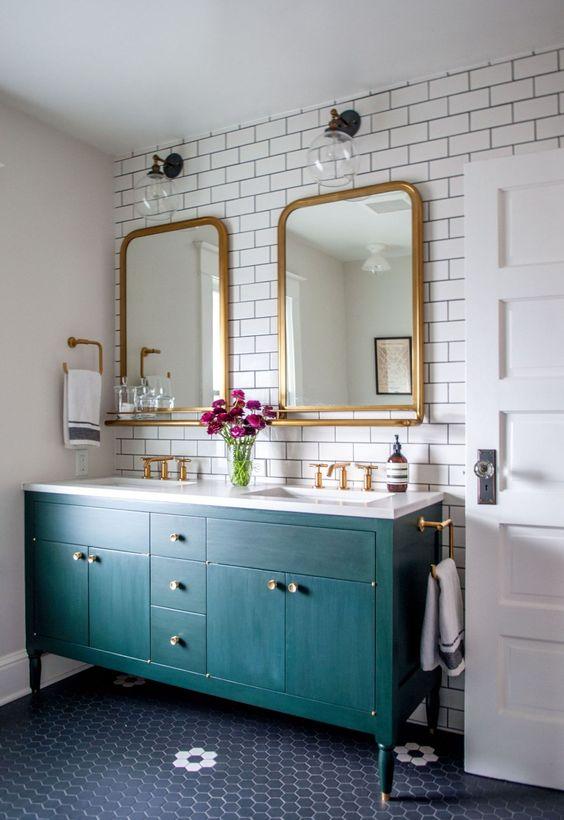 un mobile da bagno verde acqua con maniglie in ottone aggiunge stile e colore allo spazio