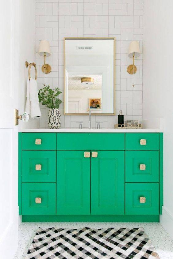 una vanità verde brillante con maniglie quadrate e tocchi in ottone è un'idea super audace per abbellire uno spazio neutro