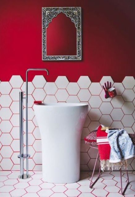 un muro rosso caldo e uno stucco rosso caldo che accentua le piastrelle esagonali sul muro e sui pavimenti