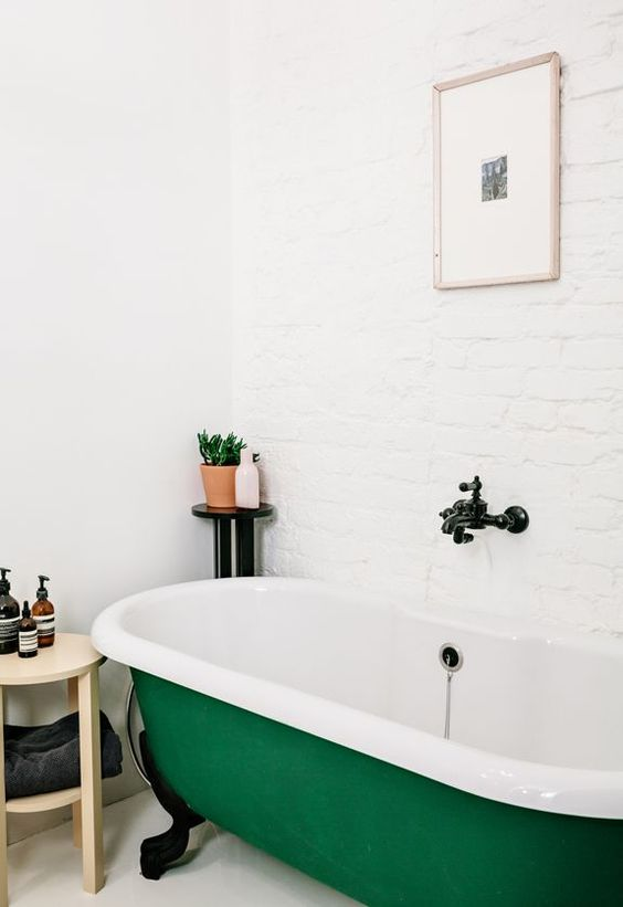 una vasca da bagno con piedini color smeraldo fa una dichiarazione audace nello spazio e lo abbellisce immediatamente
