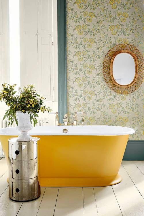 una vasca ovale gialla brilla di colore nello spazio e fa una dichiarazione in questo bagno