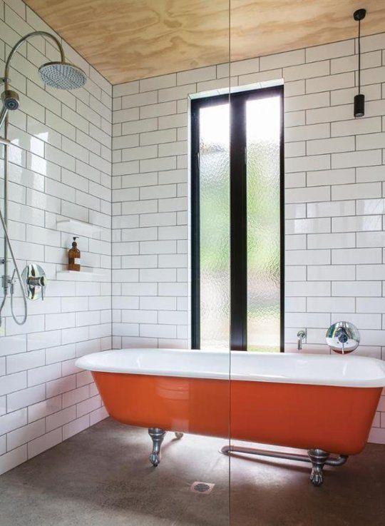 una vasca da bagno arancione con piedini è un'idea fresca e semplice per aggiungere colore allo spazio