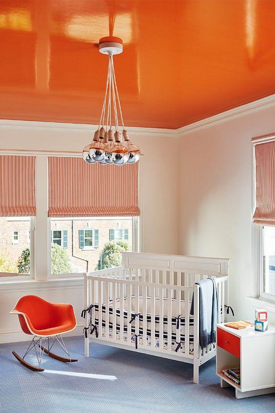 un soffitto arancione brillante, una sedia e un cassetto abbinati per creare una stanza dei bambini audace e accogliente