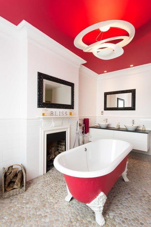 un soffitto rosso caldo e una vasca da bagno echeggiante rendono lo spazio audace e aggiungono personalità allo stesso tempo