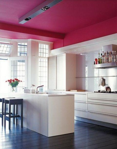 una cucina neutra evidenziata con un soffitto bordeaux per separarla visivamente dal resto dello spazio