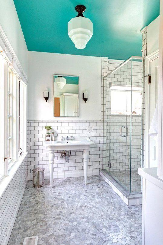 un bagno neutro arricchito da un audace soffitto color acqua che porta il colore e rende lo spazio non noioso