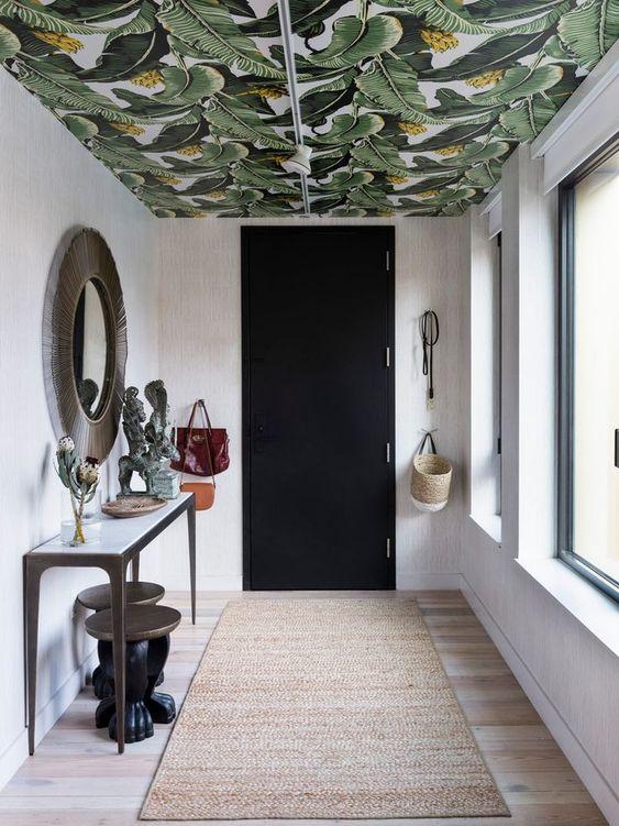 un ingresso con un soffitto luminoso ricoperto di carta da parati con stampa di foglie tropicali che aggiunge colore e stampa allo spazio