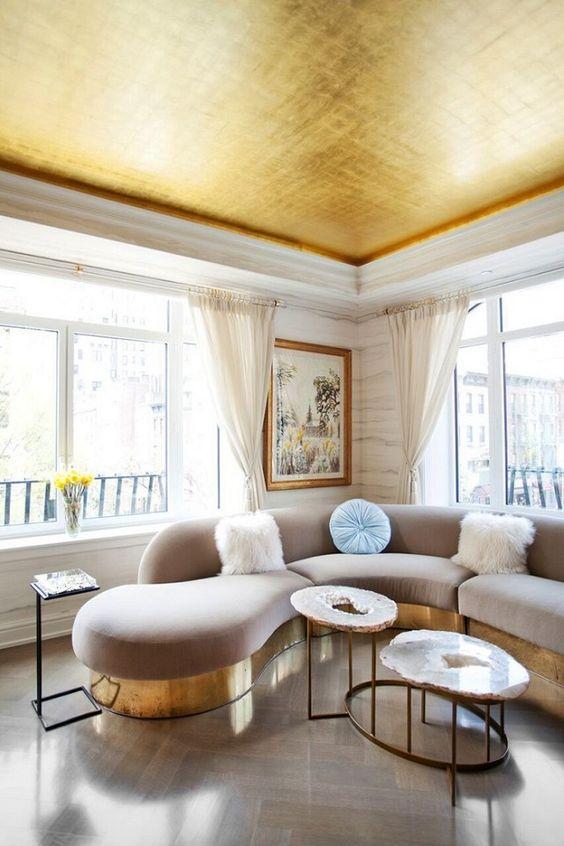 un soffitto in oro lucido riecheggia con le basi dei mobili e rende lo spazio più glam
