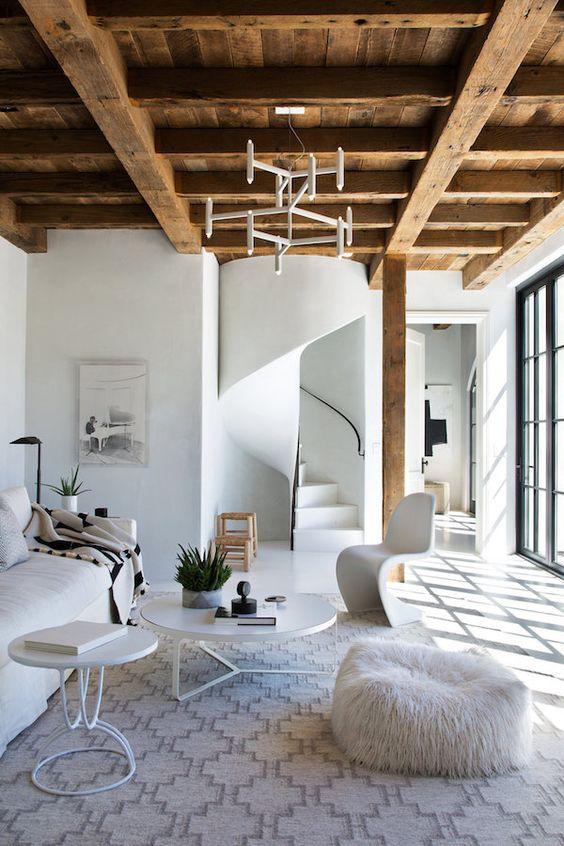un soffitto in legno rustico con travi è una caratteristica calda che aggiunge intimità a questo spazio tutto bianco