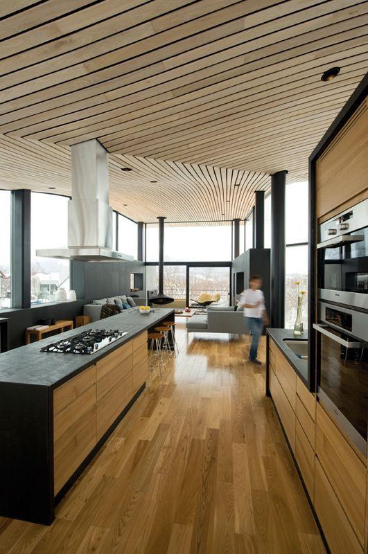 un soffitto in legno di assi scultorei conferisce un'atmosfera spigolosa allo spazio e contrasta con mobili e tubi neri